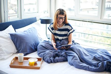 デジタル タブレットのベッドを読む若い女性 写真素材