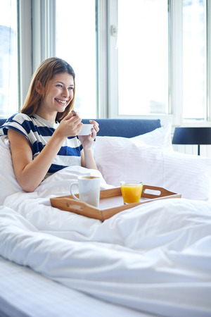Young woman eating breakfast in bed
