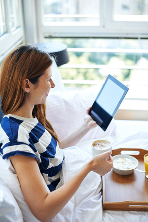 Young woman drinking coffee and reading digital tablet in bed