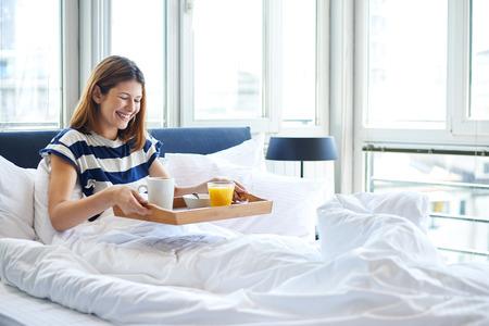 petit dejeuner: Jeune femme tenant son petit déjeuner au lit Banque d'images