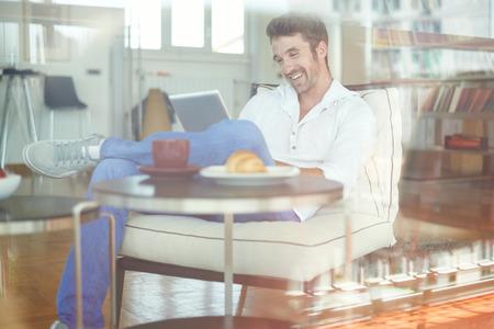 felicidad: Hombre que se relaja con tableta digital Foto de archivo