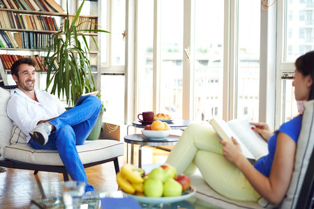 he: Couple sitting in living room, talking, he is holding tablet, she is holding book
