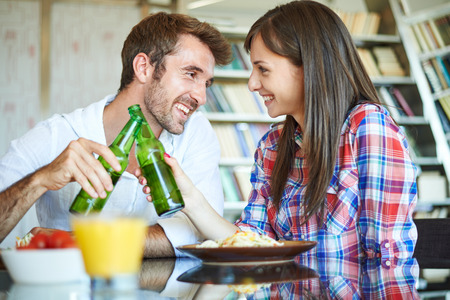 pareja comiendo: Couple eating spaghetti and cheers with beer Foto de archivo