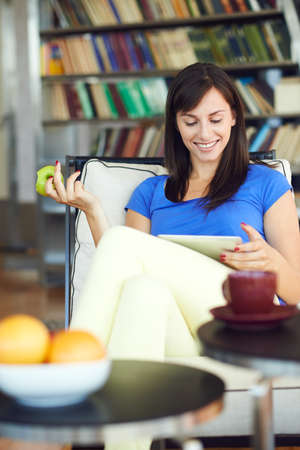 topicality: Young woman eating apple and surfing internet over digital laptop in apartment