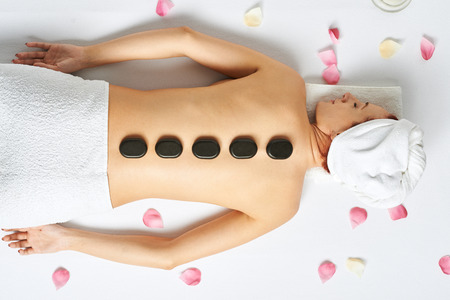 Frau mit heißen Steinen auf dem Rücken in Spa-Salon Standard-Bild - 56858833