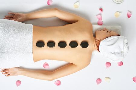 Vrouw met hete stenen op haar rug in spa salon