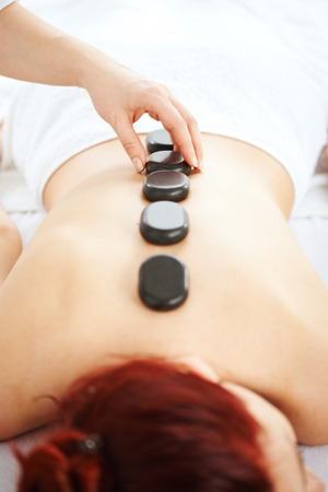 hot stones: Woman having hot stones on her back in spa salon