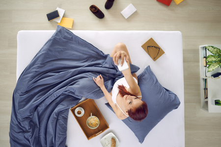 background person: Young woman making selfie in the bed, aerial view Stock Photo