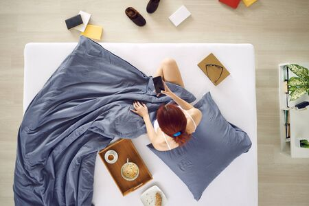 woman on phone: Woman holding mobile phone in the bed, aerial view Stock Photo