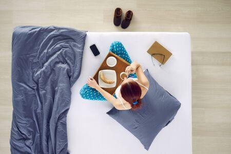 mujer en la cama: Consumición de la mujer taza de café en la cama, vista aérea Foto de archivo