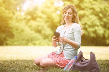 mujeres sentadas: Joven mujer sentada en un parque y enviar mensajes de texto a través del teléfono móvil Foto de archivo