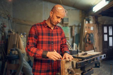 Carpenter measuring wood Banco de Imagens