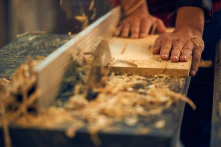 Carpenter cutting wood on circular saw Stock Photo