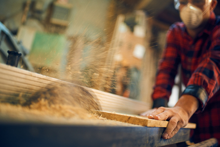 Carpenter cutting wood on circular saw Stockfoto