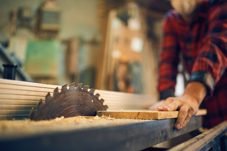 Carpenter cutting wood on circular saw Stock Photo