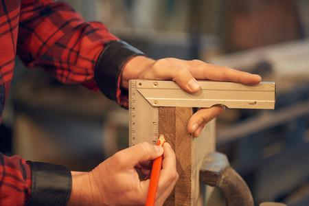 Carpenter measuring wood 스톡 콘텐츠