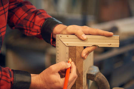 Carpenter measuring wood Foto de archivo