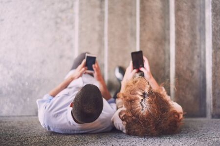 leaned: Couple using smart phones leaned on the wall, focus on their heads Stock Photo