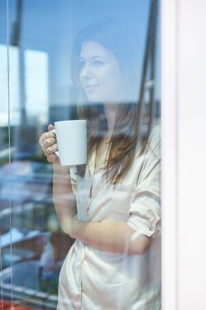 woman window: Smiling woman near window with cup of coffee Reflection of city in window Stock Photo