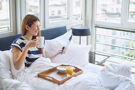 Pretty woman sitting in bed, eating breakfast