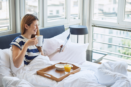 Mooie vrouw zitten in bed, eten van het ontbijt