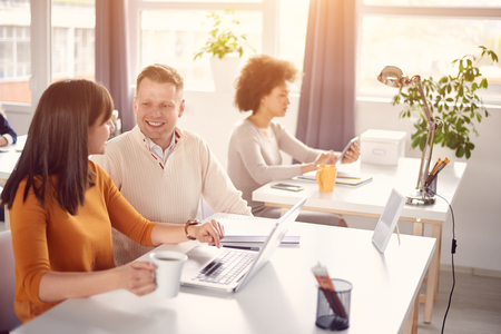 Young happy people discussing business issues in modern light office Stock Photo