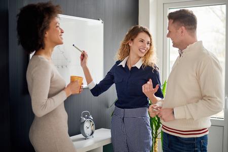 Jongeren voor whiteboard in modern kantoor
