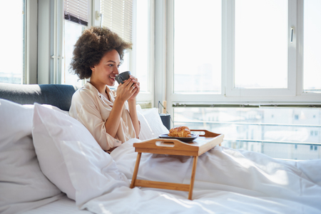 Young woman sitting on bed, eating breakfast