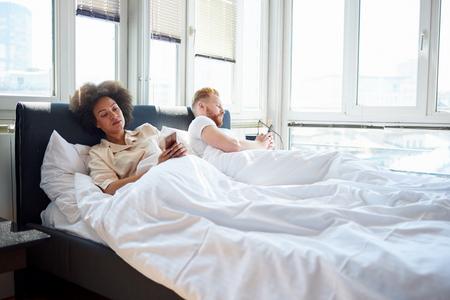 Jong stel met behulp van mobiele telefoons en liggend in bed terwijl ze elkaar negeren