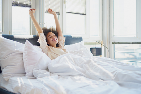 Young woman stretching in bed