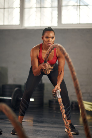Woman working out with ropes in gym