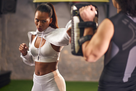 Young woman practicing boxing, coach is holding the dummy