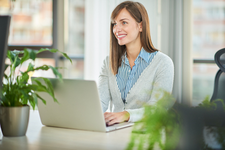 Young smiling Caucasian businesswoman dressed smart casual sitting in office and using laptop. Start up business concept.