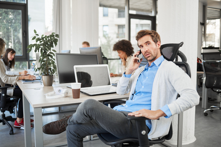 Successful CEO with serious facial expression talking on the phone while sitting in office. In background employees working.