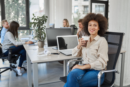 Smiling mixed race CEO sitting at office and drinking coffee while looking at camera. In background employees working. Stock fotó