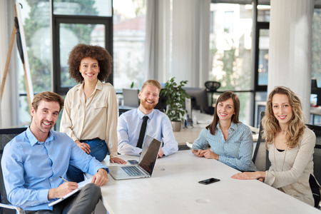 Kleine Gruppe von Geschäftsleuten, die im Büro posieren. Geschäftskonzept starten. Multiethnische Gruppe. Standard-Bild