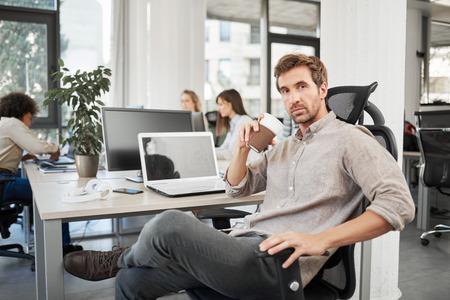 PDG avec une expression faciale sérieuse assis au bureau et buvant du café à emporter. En arrière-plan les employés travaillent.