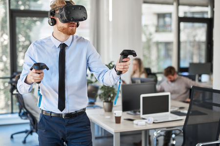 Employee in formal wear trying out VR technology in office. In background other employees working.