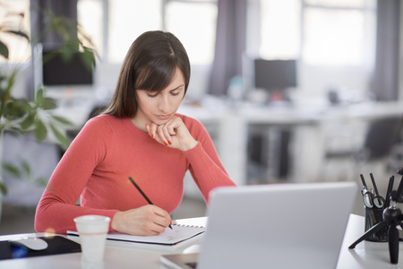 Charming Caucasian businesswoman sitting in moderna office and taking notes in notebook. In front of her laptop. Stock Photo - 120587772