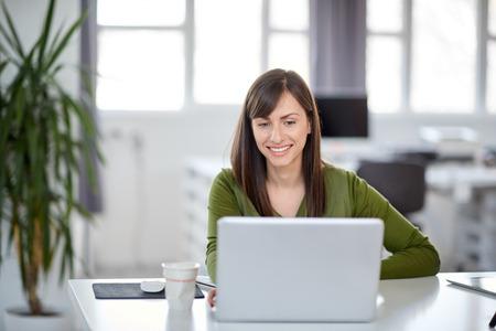 Hermosa empresaria caucásica sonriente sentada en la oficina moderna y usando la computadora portátil. Foto de archivo