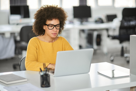 Serious mixed race businesswoman dressed casual sitting in modern office and using laptop. Stock Photo - 122301527