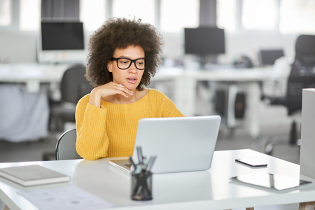 Serious mixed race businesswoman dressed casual sitting in modern office and using laptop. Stock Photo - 122301532