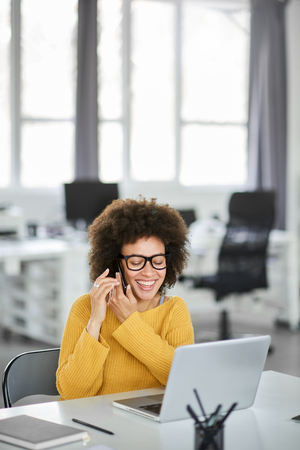 Cute mixed race businesswoman dressed casual sitting in modern office and using smart phone. Stock Photo
