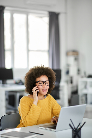 Charming mixed race businesswoman dressed casual using smart phone and laptop at the same time while sitting in modern office. Stock Photo - 122301496