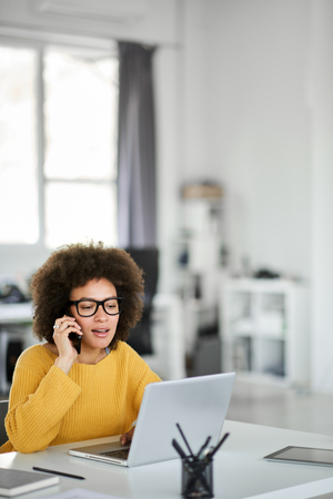 Charming mixed race businesswoman dressed casual using smart phone and laptop at the same time while sitting in modern office. Stock Photo