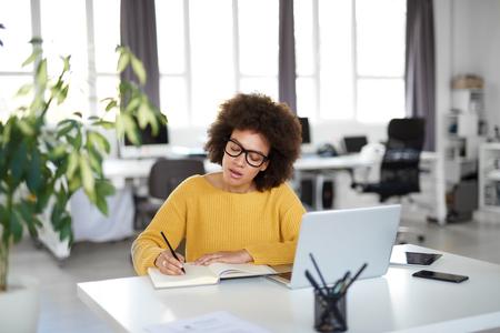 Attraktive gemischte Geschäftsfrau kleidete sich beiläufig, Notizen im Notizbuch beim Sitzen im modernen Büro zu machen Auf dem Schreibtisch Laptop, Tablet und Smartphone.
