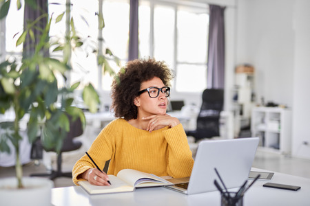 Attractive mixed race businesswoman dressed casual taking notes in notebook while sitting in modern office. On desk laptop, tablet and smart phone. Stock Photo - 122301467