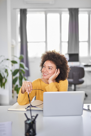 Charming mixed race businesswoman dressed casual holding eyeglasses and looking away while sitting in modern office. Stock Photo