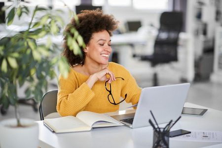 Smiling mixed race businesswoman holding eyeglasses and looking at laptop while sitting in modern office.