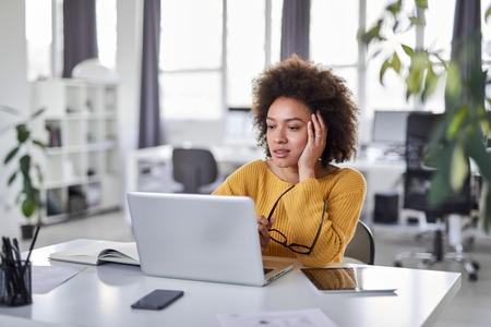 Jolie femme d'affaires métisse habillée de manière décontractée en pensant à la résolution d'un problème tout en étant assise dans un bureau moderne.